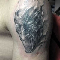 Simple black ink upper arm tattoo of monster mask