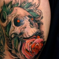 Skull with pink rose in mouth tattoo