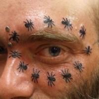 Small black-ink ant tattoo around eye