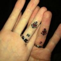 piccole ancore nere con cuoricini rossi tatuaggio per innamorati sulle dita