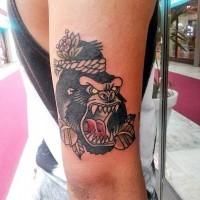 Small dreadful gorilla head in hat tattoo on upper arm