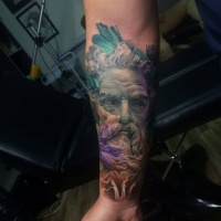 Statue face tattoo on forearm