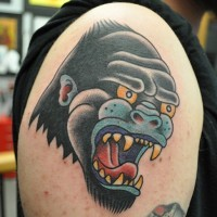 Super old school colorful gorilla head tattoo on upper arm