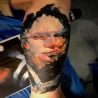 Surrealism style colored biceps tattoo of human face