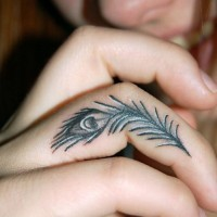 Tiny peacock feather tattoo on finger
