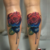 Two colors red and blue rose tattoo on leg