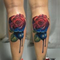 Tatuaggio a due colori rosso e rosa blu sulla gamba