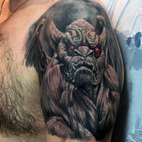 Very realistic looking colored gargoyle with red eyes tattoo on upper arm