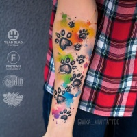 Watercolor paw prints tattoo on forearm