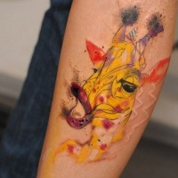 Wonderful girly yellow giraffe head tattoo on arm
