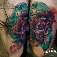 Abstract style colored biceps tattoo of human skull stylized with mystic eye