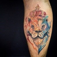 Abstract style multicolored lion face tattoo on leg stylized with crown