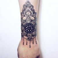 Accurate blackwork style wrist tattoo of floral ornament