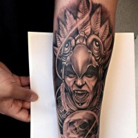 Accurate detailed looking black and white forearm tattoo of tribal pries and human skull
