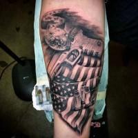 Tatuaje en el brazo, pistola con balas y bandera americana