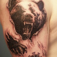 Angry bear skin rip tattoo on shoulder