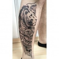 Art style black ink leg tattoo of lion head with various ornaments