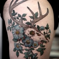 Art style colored thigh tattoo of animal skull with violet flowers