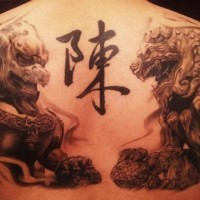 Asian traditional detailed upper back tattoo of lion statues with symbol