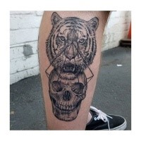 Awesome 3D style leg tattoo of tiger head with human skull