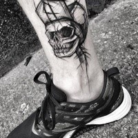 Awesome black ink ankle tattoo painted by Inez Janiak ankle tattoo of human skull with hat