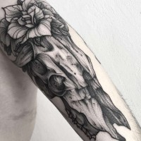 Awesome vintage style black ink animal skull tattoo on arm combined with big flower