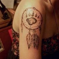 Tatuaggio tribale sul deltoide la traccia della zampa del orso su dreamcatcher