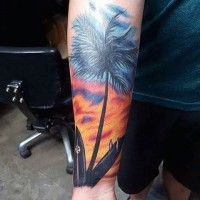Beautiful colored lonely palm tree with surfing boards tattoo on arm