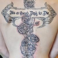 Tatuaje en la espalda, cruz decorado con flores y inscripción