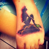 Beautiful little colored foot tattoo of mermaid sitting on stone