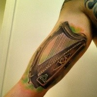 Beautiful looking colored arm tattoo of Celtic harp