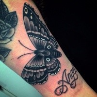 Beautiful looking leg tattoo of big butterfly with lettering