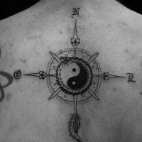 Big black and white back tattoo of compass stylized with Yin Yang symbol