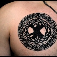 Big black ink Celtic style circle tattoo on chest stylized with tree