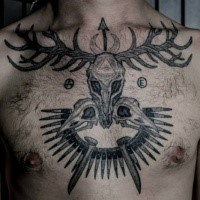 Big black ink chest tattoo of animal skull with feather
