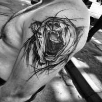 Big black ink painted by Inez Janiak upper arm tattoo of roaring bear