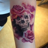 Big pink colored romantic flowers tattoo with skull on arm