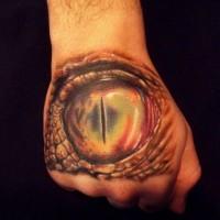 Big realistic looking dragon eye tattoo on hand