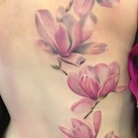 Big size delicate and tender pale pink detailed realistic flowers tattoo on woman's back