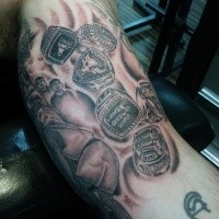Black and gray style biceps tattoo of various finger rings