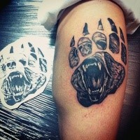 Black and gray style big animal paw shaped leg tattoo stylized with bear face