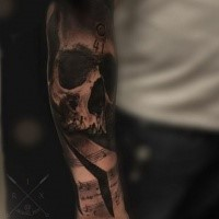 Black and gray style colored arm tattoo of human skull with music notes