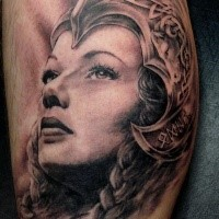 Black and gray style colored leg tattoo of Celtic woman with helmet