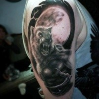 Black and gray style colored shoulder tattoo of werewolf and large moon