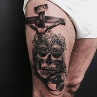 Black and gray style colored thigh tattoo of Jesus on cross with skull and mask