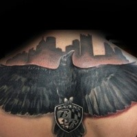 Black and gray style colored upper back tattoo of big crow with emblem and lettering