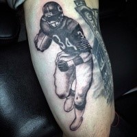 Black and gray style detailed biceps tattoo of American football player