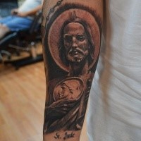 Black and gray style detailed forearm tattoo of Jesus portrait