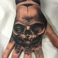 Black and gray style detailed hand tattoo of monster skull with eye