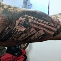 Black and gray style detailed looking biceps tattoo of great revolver and lettering
